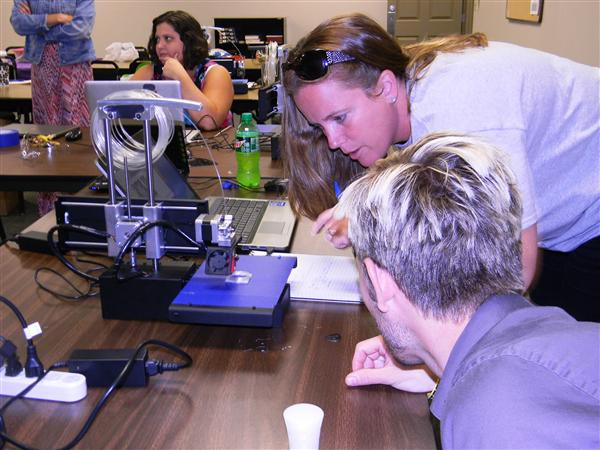 Two participants watch the 3D printer begin to print an object.